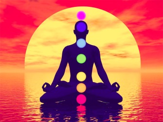 Silhouette of a man meditating with seven colorful chakras upon ocean by red sunset
